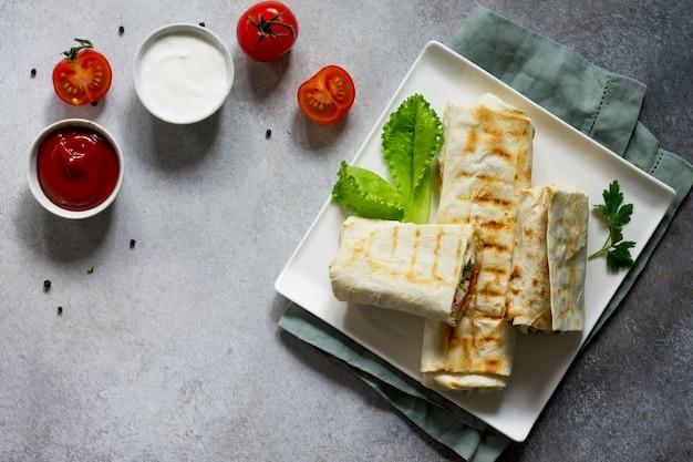 シャワルマのピタパンとチキンのグリルドネルケバブの新鮮な野菜とクリームソース