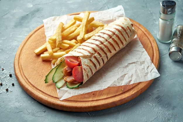 Shawarma roll in pita with chicken, tomatoes, cucumber and lettuce. street food
