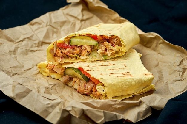Shawarma roll with chicken and vegetables in pita bread on a black background