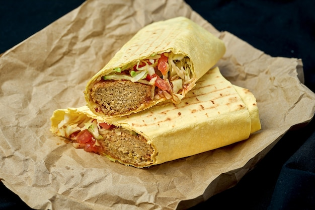 Shawarma roll with falafel and vegetables in pita bread on a black background