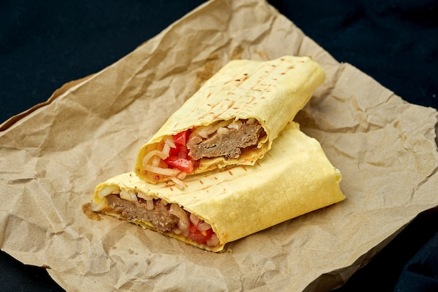 Shawarma roll with kebab and vegetables in pita bread on a black background