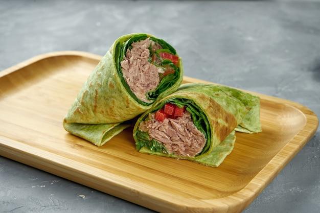 참치, 피망, 당근, 샐러드와 shawarma 롤은 회색 테이블에 나무 보드에 녹색 피타 빵에 나뭇잎. 클로즈업, 선택적 초점