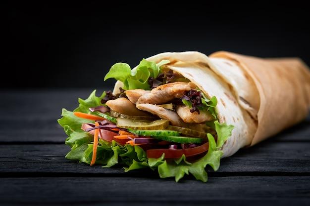 Шаурма, завернутая в лаваш, сырое мясо на гриле с луком, зеленью и овощами на деревянной черной поверхности