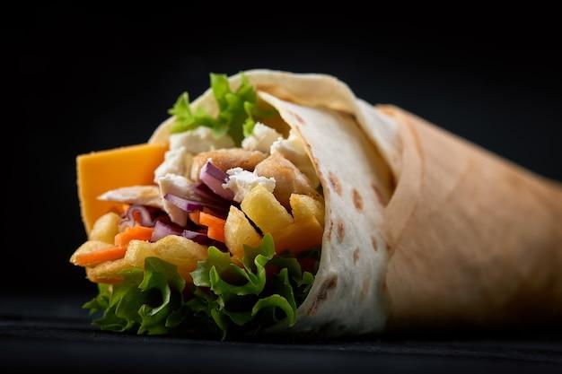 シャワルマは、木製の黒い表面にタマネギ、ハーブ、野菜を添えたラヴァッシュ、湿った焼き肉で巻いた。