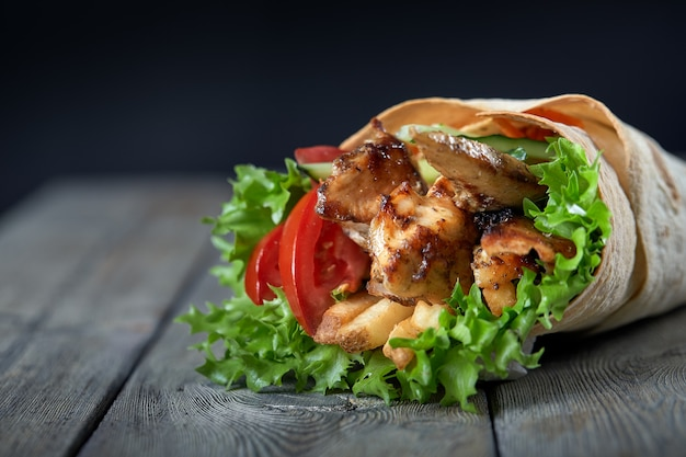 Шаурма, завернутая в лаваш с жареным мясом и овощами на деревянном фоне
