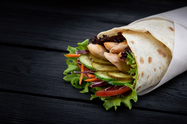 Shawarma rolled in lavash, moist grilled meat with onion, herbs and vegetables on wooden black surface