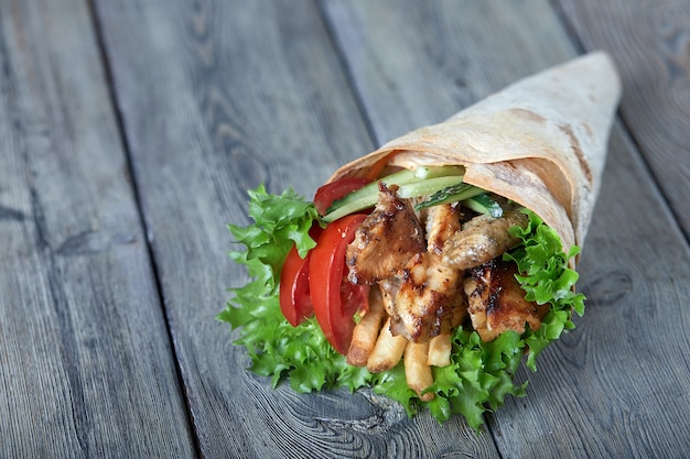 Shawarma rolled in lavash, moist grilled meat with onion, herbs and vegetables