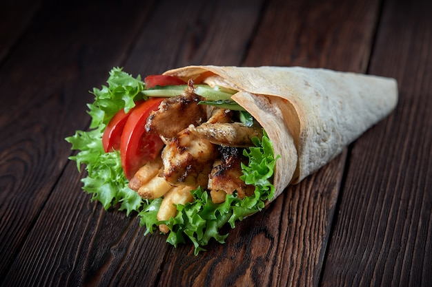 Shawarma rolled in lavash with grilled meat and vegetables on wooden background