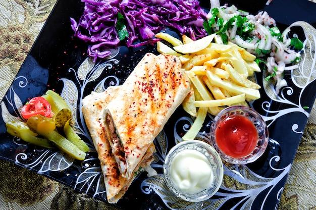 Shawarma sandwich fresh roll of lavash (pita bread) chicken beef shawarma traditional middle eastern snack.