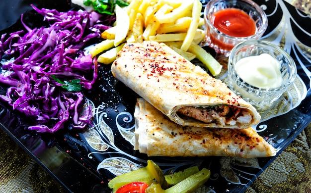 シャワルマサンドイッチラバッシュ(ピタパン)チキンビーフシャワルマの新鮮なロール伝統的な中東のスナック。