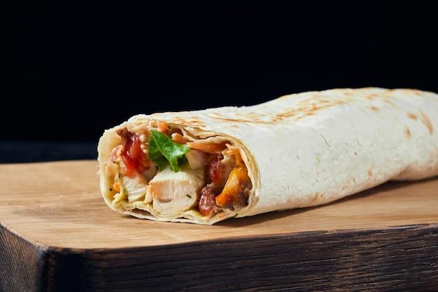 Сэндвич с шаурмой. свежий рулет из тонкого лаваша с начинкой из куриного мяса, сыра, зелени на деревянной доске. традиционная восточная закуска.