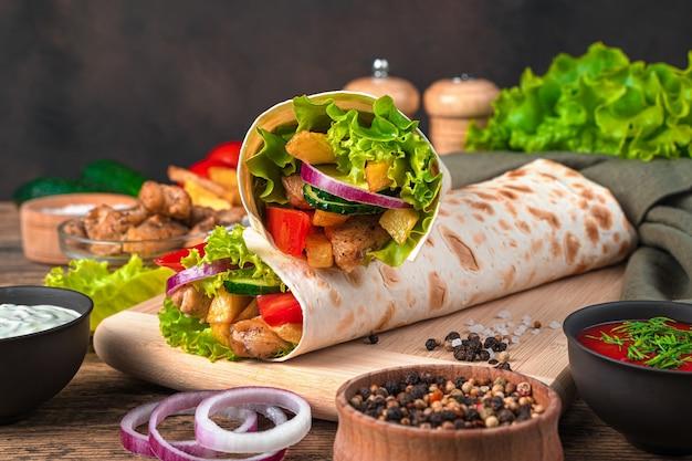 Шаурма с курицей, картофелем фри и крупным планом овощей на коричневой стене. вид сбоку, копия пространства. быстрое питание.