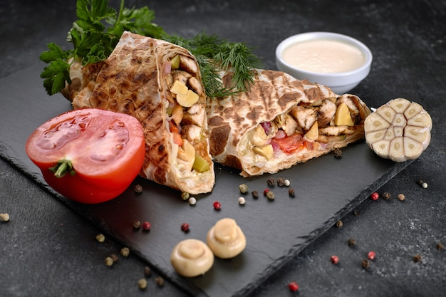 Shawarma with chicken meat, with sauce, onions, pickles, tomato, garlic, herbs and mushrooms champignons, on slate, against a dark concrete background