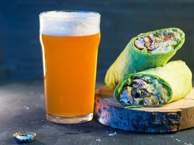 Shawarma with chicken, vegetables and sweet sauce, a glass of light unfiltered beer