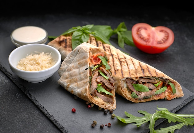 Shawarma with meat, cutaway, with sauce, tomatoes, cheese, herbs and garlic, on black slate, on a black background