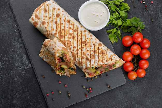 Shawarma with meat, cutaway, with sauce, tomatoes, cheese, herbs and garlic, on black slate