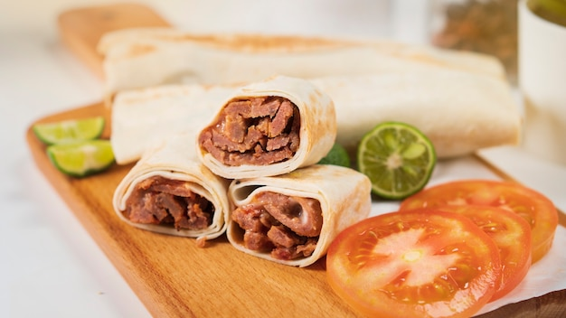 Shawarma with meat, mayonnaise, tomato and lime on a wooden cutting board