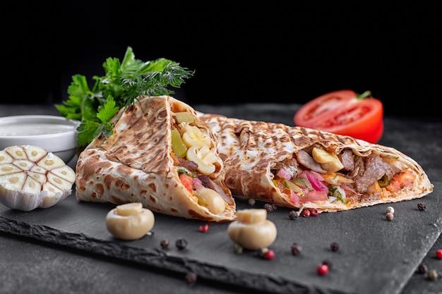 Шаварма с мясом, с соусом, луком, солеными огурцами, помидорами, чесноком, шампиньонами из трав и грибов, на грифельной доске, на темном бетонном фоне