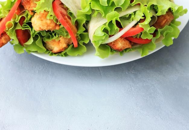 白い皿にドナーケバブ。肉、玉ねぎ、サラダ、灰色の背景上のトマトのshawarma。