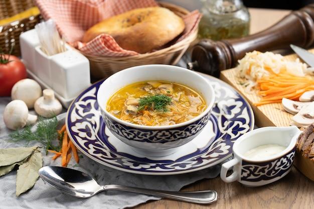 Щи со сметаной - традиционный русский овощной суп из капусты, картофеля, моркови и грибов в тарелке с традиционным узбекским