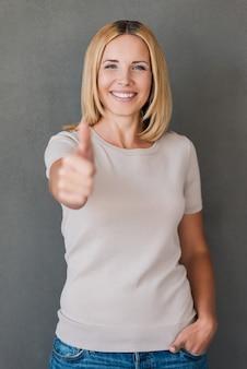 彼女はそれを承認します!親指を立てて笑顔で元気な成熟した女性