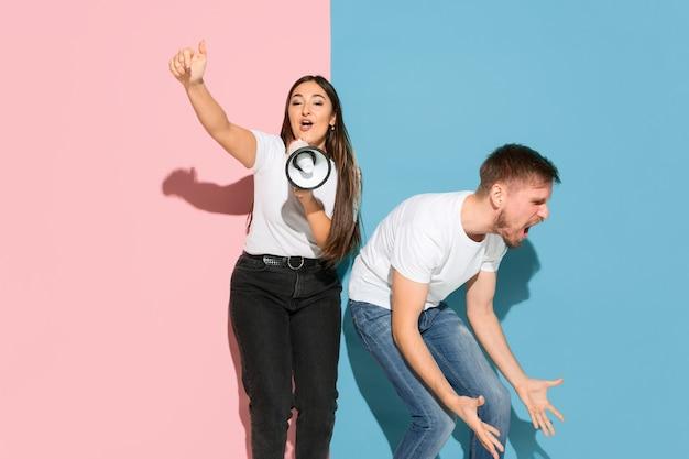 Она звонит в мегафон, он зол. молодой и счастливый мужчина и женщина в повседневной одежде на розовой, синей двухцветной стене. понятие человеческих эмоций, мимики, отношений, рекламы. прекрасная пара.