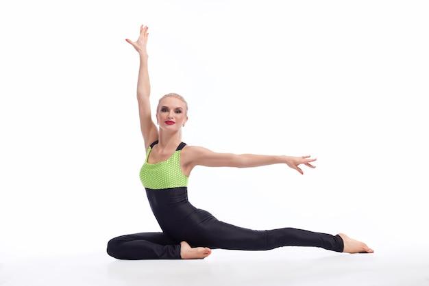 그녀는 필요한 것을 가지고 있습니다. 흰색 배경 copyspace 훈련 체육관 체조 체조 개념에 대해 바닥에 우아하게 앉아 화려한 금발 여성 체조