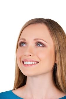 Она счастливая мечтательница. красивая молодая женщина улыбается и смотрит вверх, пока изолирована на белом