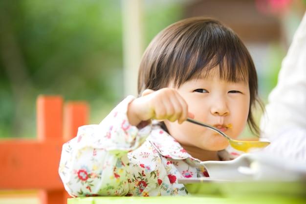 그녀는 엄마 옆에 앉아 수프를 먹는 사랑스러운 아이입니다.