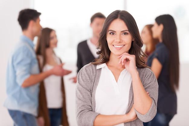 Она руководитель группы. уверенная молодая женщина, держащая руку на подбородке и улыбаясь, пока группа людей общается на заднем плане