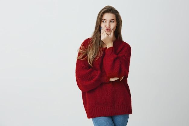 Она собирается позвонить тебе. портрет красивой стройной кавказской девушки в свободном свитере, сжимающем рот и смотрящем в сторону, желающем или тоскующим по чему-то. девушка заинтересована пойти на мероприятие