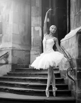 She is a living art. vertical monochrome shot of a beautiful ballerina standing in ballet pose on stairs of an old castle soft focus