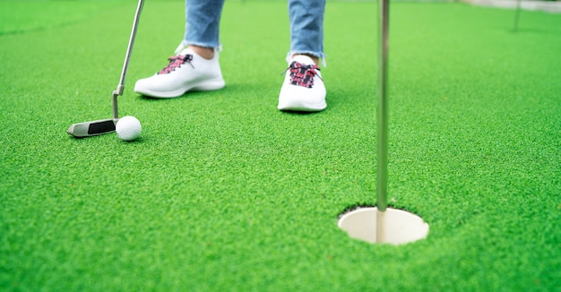 She is playing golf in an artificial turf.