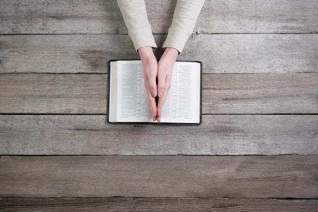 彼女は木製のテーブルの上で聖書を読み、祈っています
