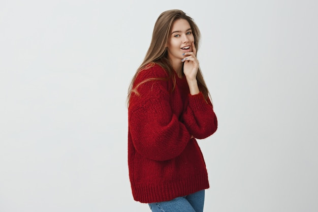 She is real heartbreaker. indoor shot of attractive female student standing in profile, smiling  while touching chin and thinking about something, being curious if plan will be fulfilled