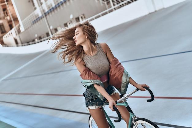 그녀는 너무 아름답습니다! 야외에서 자전거를 들고 서 있는 동안 눈을 감고 있는 평상복을 입은 매력적인 젊은 여성