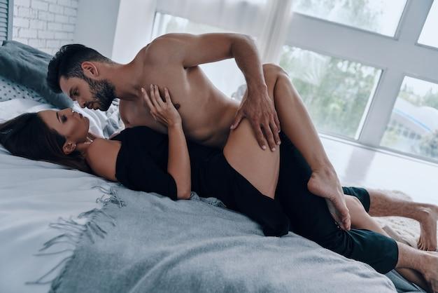 Она центр его вселенной. красивая молодая пара собирается заняться сексом, лежа в постели