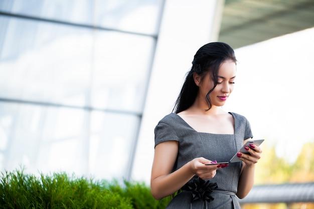 彼女は支払いにゴールドクレジットカードと携帯電話を使用しています
