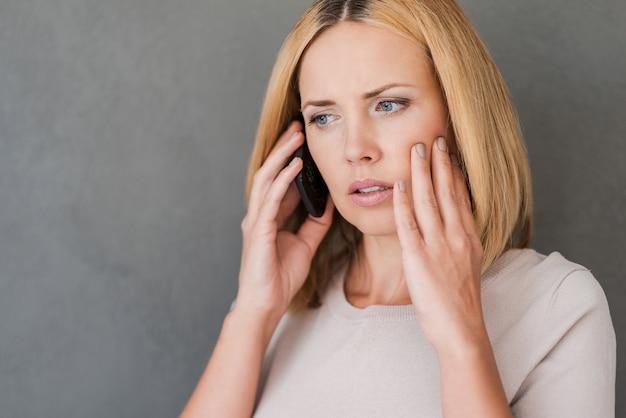 彼女はちょうど悪い知らせを受けた。携帯電話で話し、否定性を表現する欲求不満の成熟した女性