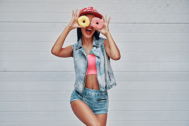 She do not know what the boredomis. playful young women holding donuts against her eyes and smiling while standing against the garage door