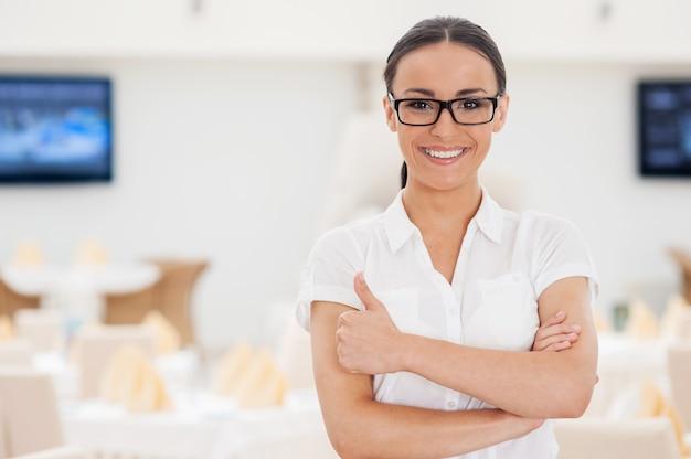 Она знает все о ресторанном бизнесе. красивая молодая женщина в строгой одежде, скрестив руки и улыбаясь, стоя в ресторане