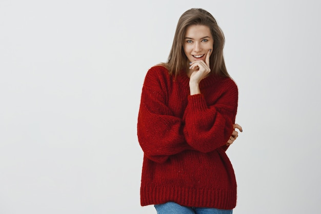 She knows exactly how seduce with gaze. sassy good-looking flirty european woman in loose red winter sweater biting finger smirking having interesting idea in mind over