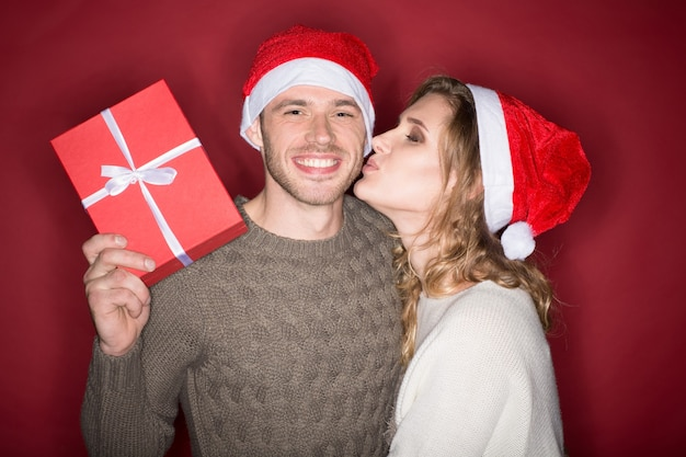 She knows what he needs. studio shot of a beautiful blonde woman kissing her man on the cheek man holding a present and smiling joyfully both wearing christmas hats