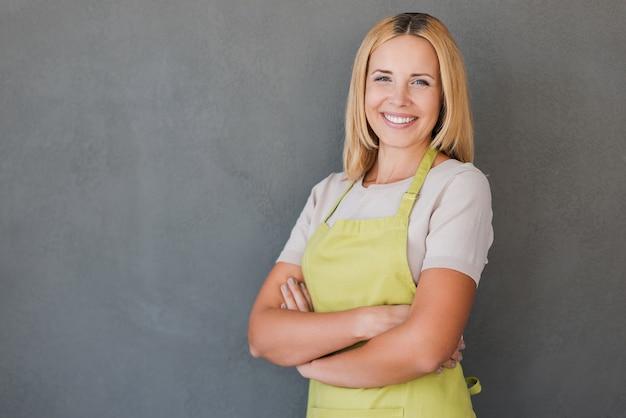 彼女は自分の仕事が大好きです。腕を組んでカメラを見ながら緑のエプロンで笑顔の成熟した女性