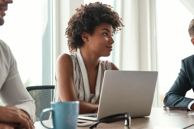 Она любит свою работу. красивая африканская женщина сидит на деловой встрече и улыбается. многокультурная команда