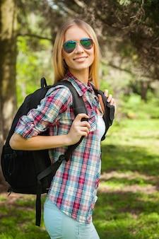 彼女はハイキングが大好きです。自然の中で立っている間彼女のバックパックを運び、カメラを見ている美しい若い女性