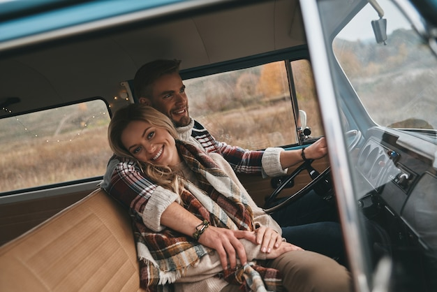 She means everything to him. beautiful young couple embracing and smiling while sitting in retro style mini van