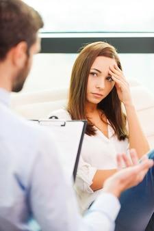 그녀는 위로가 필요합니다. 걱정된 젊은 여성이 의자에 앉아 머리에 손을 얹고 남성 정신과 의사가 그녀 앞에 앉아 몸짓을 하는 동안