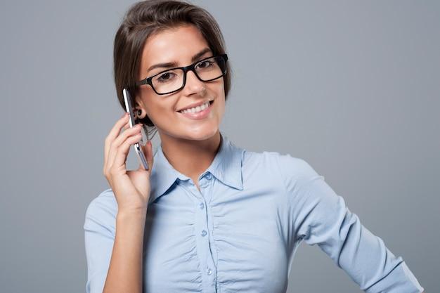 그녀는 휴대폰으로 고객과 연락하고 있습니다.