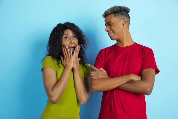 She's scared, he's laughting. young emotional african-american beautiful man and woman in colorful clothes on blue wall.